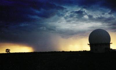 Photo showing a cloudy sky and heavy rain in the background with some clearing on either side.  Foreground right there is a raised dome structure that houses the doppler radar.