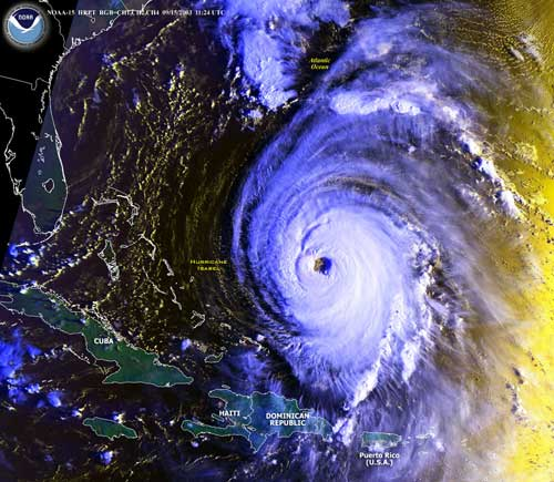 Visible imagery, Hurricane Isabel in the Atlantic Ocean, September 15, 2003. The image was taken as the sun rises, coloring the right side of the image.