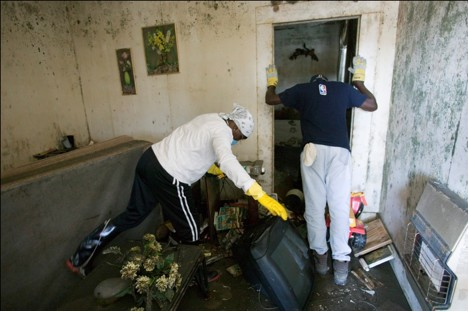 Residents of a New Orleans, LA, Lower 9th Ward home search for salvageable items in the aftermath of Hurricane Katrina (2005).
