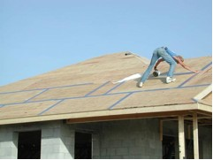 Photo of a worker installing tape over the seams in a roof's plywood to minimize water intrusion.