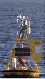 Two technicians with NOAA's National Data Buoy Center repair a weather buoy off the North Carolina coast damaged by Hurricane Katrina